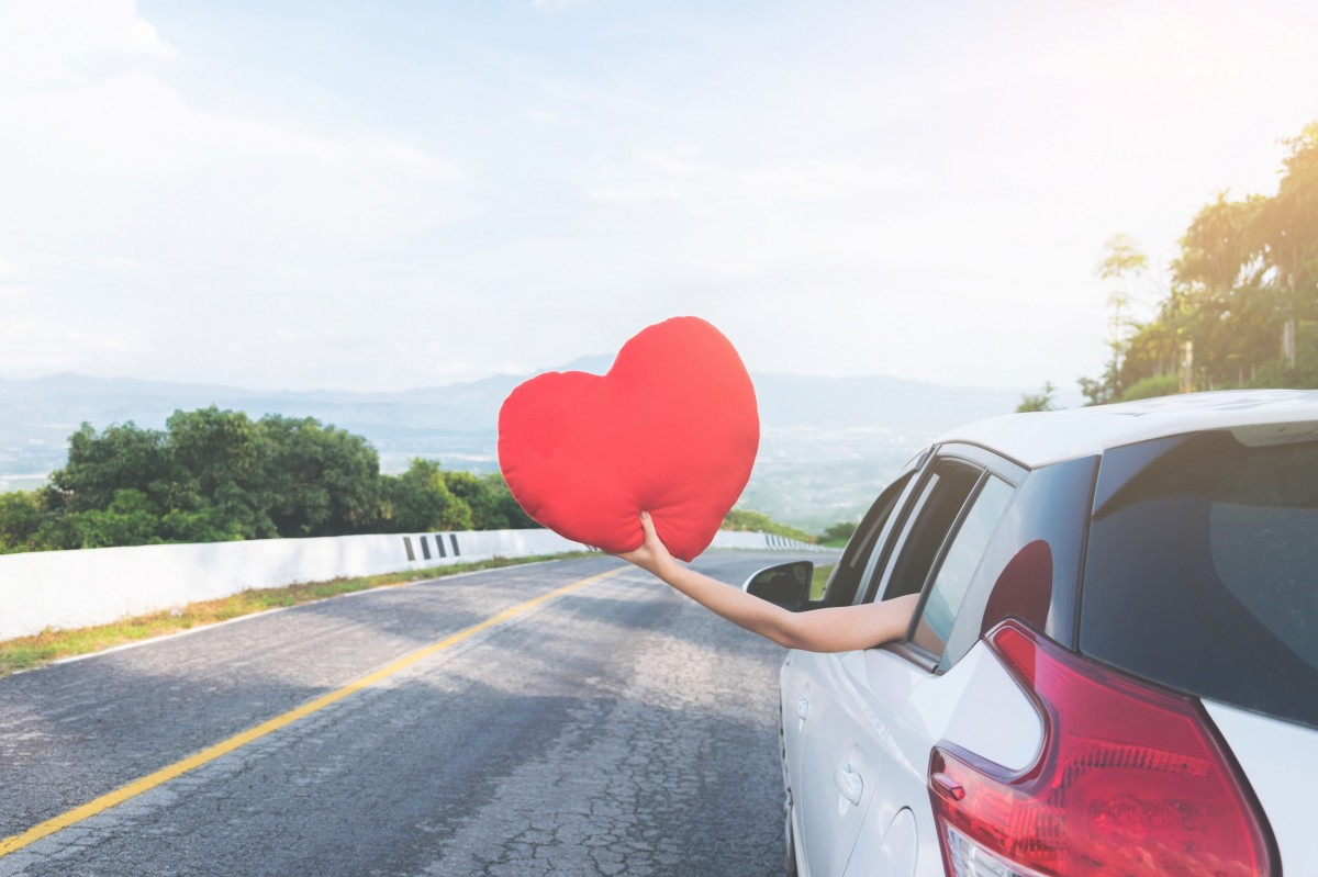 hand holding a heart shaped paper outside of car window